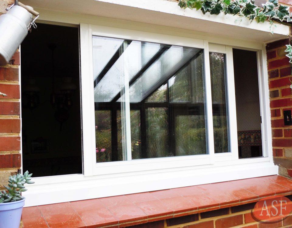 Vu extérieure de la fenêtre coulissante blanche ouverte.